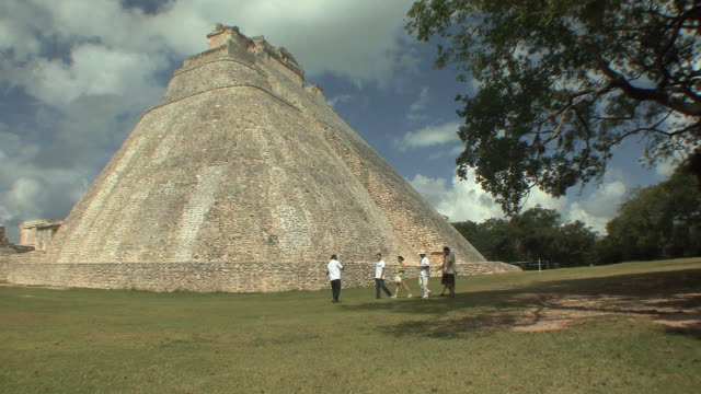 WS Group of tourists at Adivino (Pyramid of Magician) at pre-Columbian ruined city of Maya civilization / Uxmal, Yucatan, Mexico