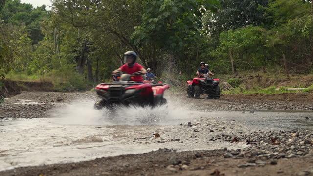 vidéos et rushes de groupe de touristes conduisant des vélos 4x4 par l'eau au costa rica - sports utility vehicle