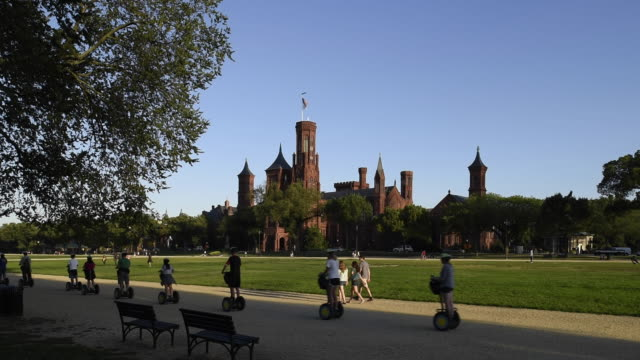vídeos de stock e filmes b-roll de a group of tourists on segways cruise past the smithsonian castle at the national mall. - instituto smithsoniano