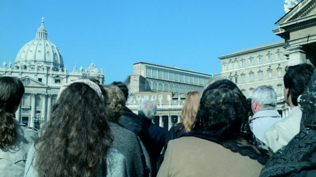 a group of tourists stand and wait at the vatican. - サンピエトロ寺院点の映像素材/bロール