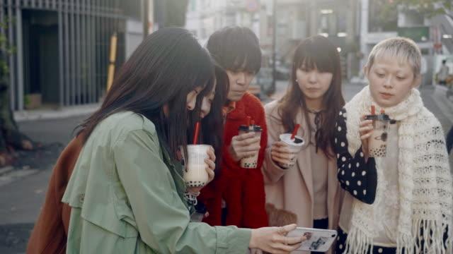 バブルティーでセルフィーを撮るトレンディな日本の若い大人のグループ - 若い女性点の映像素材/bロール