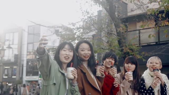バブルティーでセルフィーを撮るトレンディな日本の若い大人のグループ - ティーンエイジャー点の映像素材/bロール