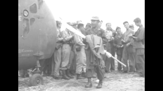 group of un military personnel gathered in field / two un officers in negotiating party making their way towards helicopter / un officer puts white... - korean war stock videos and b-roll footage