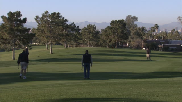 group of unidentifiable males on golf course field hole playing golf standing around sports golfing country club - clubhouse stock videos & royalty-free footage