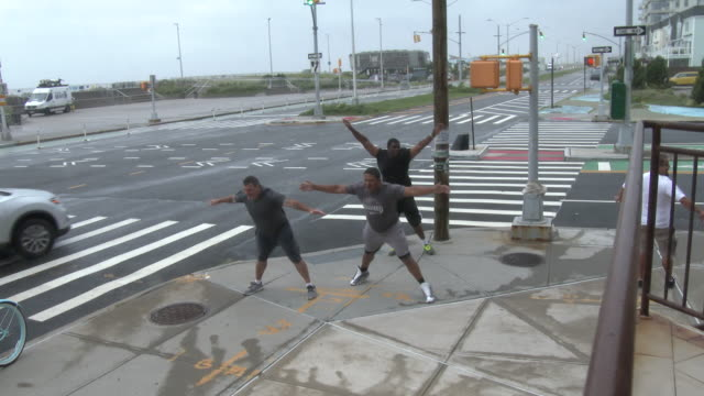 a group of unidentified men stand on the corner of beach 94th street and shore front parkway and lean into the wind as tropical storm isaias bears... - scott mcpartland stock videos & royalty-free footage