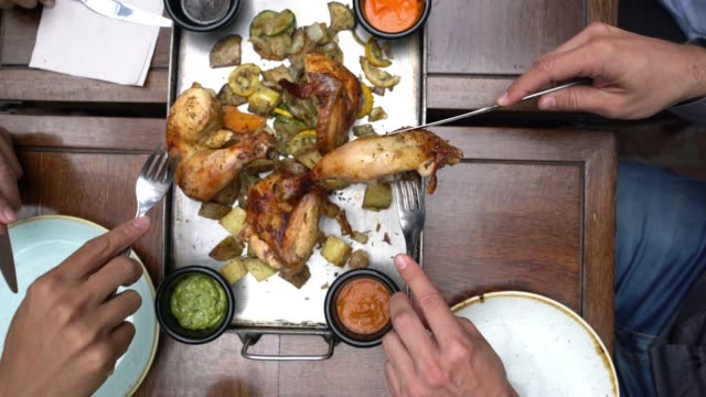 group of unrecognizable people sharing roasted chicken and each serving on their plates - colombia stock videos & royalty-free footage