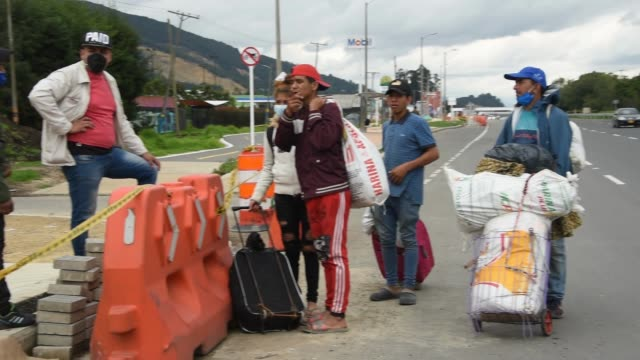 vídeos y material grabado en eventos de stock de a group of venezuelan migrants break with their belongings on the side of the highway as they travel out of the city while the world struggles... - hispanoamérica