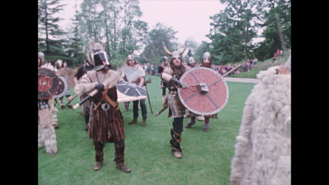 a group of vikings hit their shields and attack castle - battle stock-videos und b-roll-filmmaterial