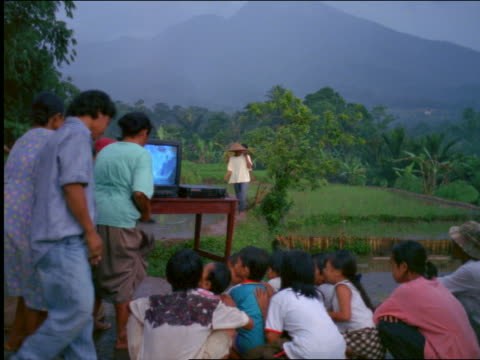 vídeos de stock, filmes e b-roll de group of villagers gathering on road to watch television / rice paddies in background / indonesia - 1990 1999