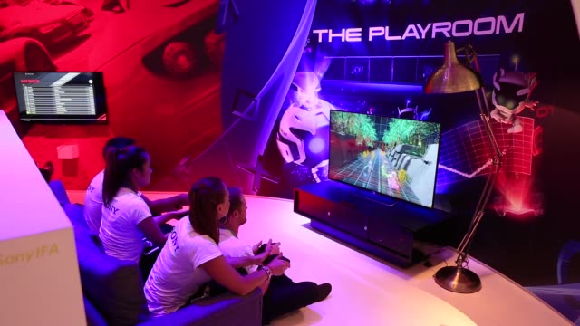 A group of visitors and employees play on Sony PlayStation 4 games consoles at the Sony Corp trade stand on the opening day of the IFA Consumer...