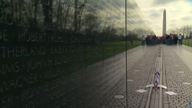 ms group of visitors standing in front of vietnam veterans memorial with washington monument / washington, district of columbia, united states - ベトナム戦争戦没者慰霊碑点の映像素材/bロール