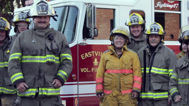pan, group of volunteer fire fighters in front of fire truck, eastville, virginia, usa - firefighter stock videos & royalty-free footage