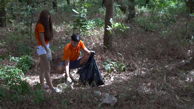vídeos de stock e filmes b-roll de group of volunteer picking trash into plastic bag for cleaning the public park in morning time - apanhar atividade física