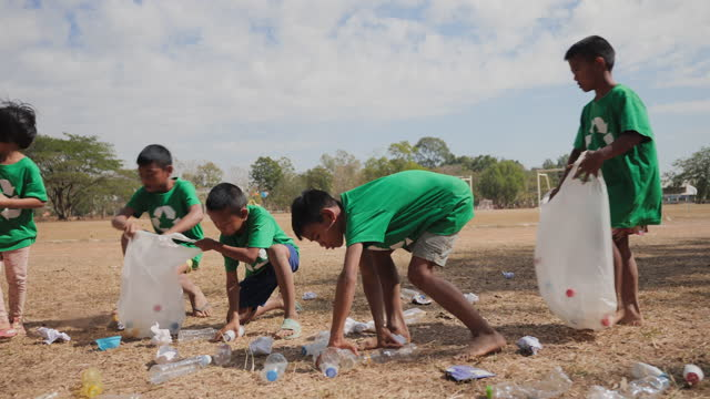 vídeos de stock e filmes b-roll de group of volunteers child pick up garbage and recyclable items during a community cleanup event. - apanhar atividade física