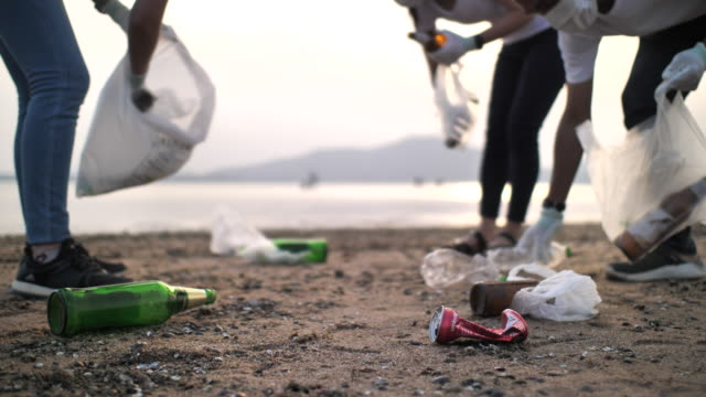 group of volunteers people with garbage bags cleaning area on the beach - altruism stock videos & royalty-free footage