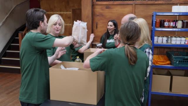 4K: Group of Volunteers sorting food into boxes in a Food Bank - Teamwork