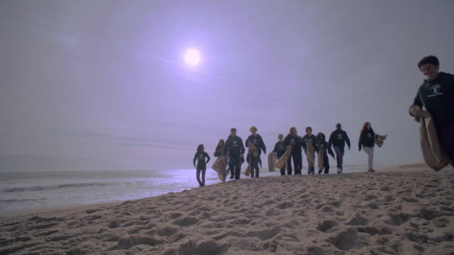 a group of volunteers walks along a beach together. - teenagers only stock videos & royalty-free footage