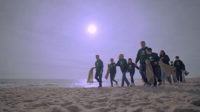 A group of volunteers walks along a beach.