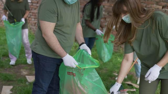 保護フェイスマスクを持つボランティアのグループは、自然を掃除します - ゴミ袋点の映像素材/bロール
