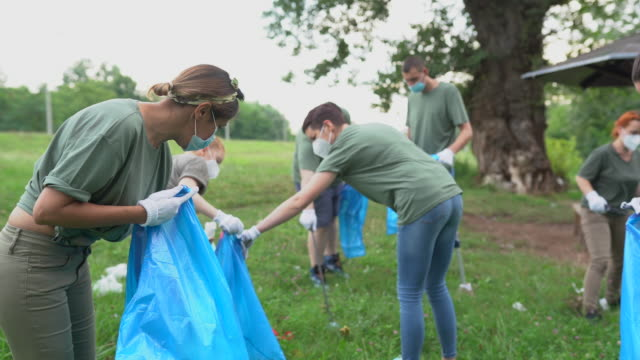 group of volunteers with surgical masks cleaning nature together - volunteer stock videos & royalty-free footage