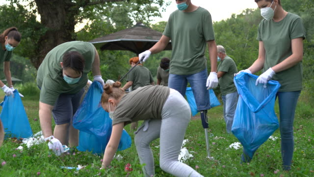 group of volunteers with surgical masks cleaning nature together - protection stock videos & royalty-free footage