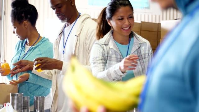 vídeos y material grabado en eventos de stock de grupo de voluntarios trabajando juntos en bani de alimentos - voluntario