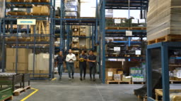 Group of warehouse employees walking through aisle