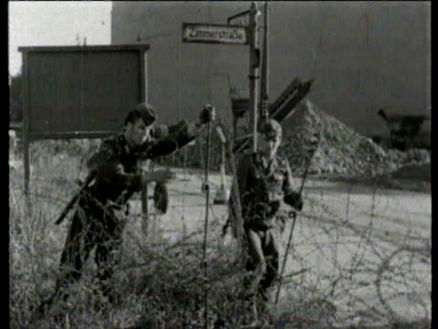 group of west berliners watch east german soldiers put up barbed wire barriers as the berlin wall is built / refugees wait / east german soldiers put... - 1961 stock-videos und b-roll-filmmaterial