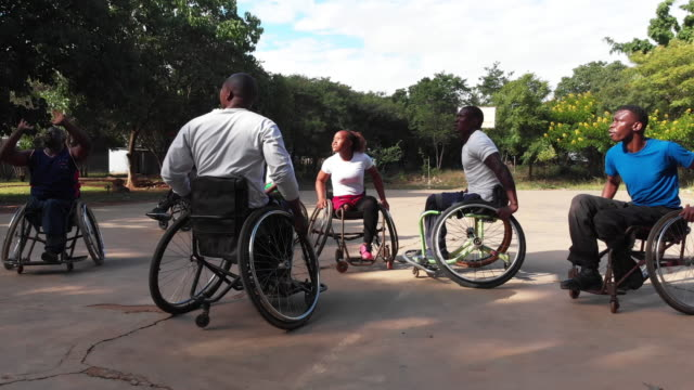 group of wheelchair basketball players playing a friendly match on a local ground - wheelchair basketball stock videos & royalty-free footage