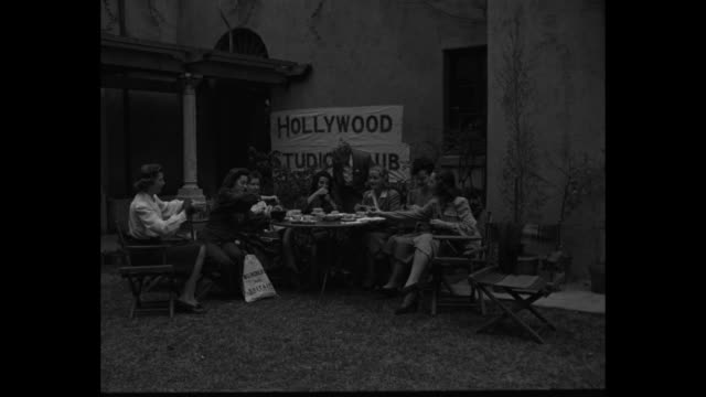 group of women at table on lawn at hollywood studio club knitting wrapping yarn drinking tea / one woman hands a cup saucer to another who has yarn... - saucer stock videos and b-roll footage