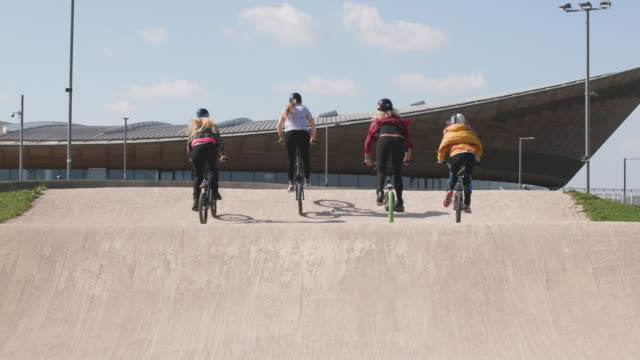 a group of women bmx riders racing their bikes together on a race track - freestyle bmx stock videos & royalty-free footage