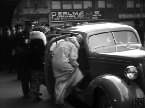 b/w 1935 group of women climbing into car / doorman closing doors / car driving off / nyc - prelinger archive stock-videos und b-roll-filmmaterial