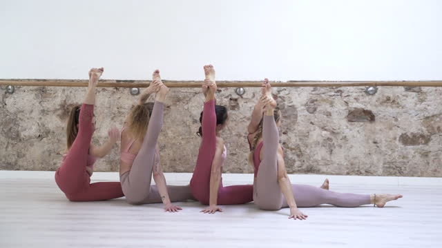 a group of women doing an acro yoga position. - barre stock videos & royalty-free footage