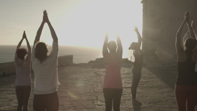 group of women doing yoga at sunrise at ancient fort by ocean in portugal - människoarm bildbanksvideor och videomaterial från bakom kulisserna