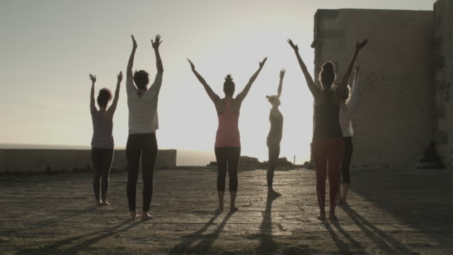 Group of women doing yoga at sunrise at ancient fort by ocean in Portugal