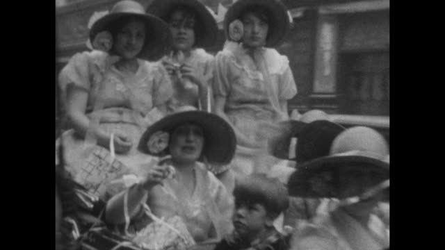 vidéos et rushes de a group of women dressed up in fancy clothes and bonnets with flowers drive by in a convertible during a carnival in buenes aires in 1927. - 1930