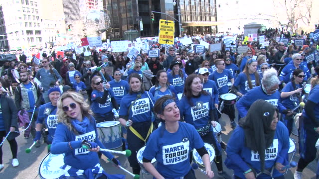 vídeos de stock, filmes e b-roll de a group of women drummers perform while marching in the protest / thousands of people many of them students march against gun violence in manhattan... - march for our lives