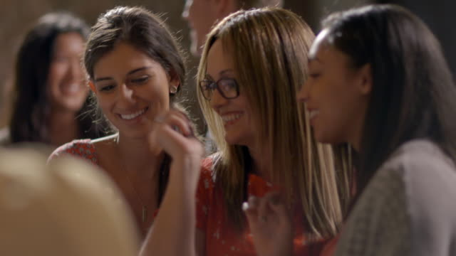 stockvideo's en b-roll-footage met group of women friends look at smartphone together at restaurant bar - druk spanning