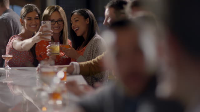 vidéos et rushes de group of women friends pose for smartphone selfies at crowded bar - collègue