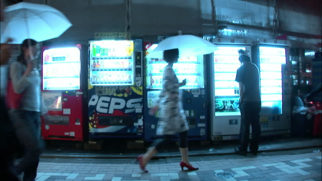 ws group of women holding umbrellas and walking in line on sidewalk past illuminated vending machine at night / tokyo, japan - people in a line stock videos & royalty-free footage