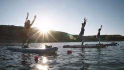 A Group of Women in Chair Pose (Utkatasana) Yoga Pose on Paddleboards on a Desert Lake Under a Clear, Blue, Sunny Sky in Western Colorado (Snooks Bottom)