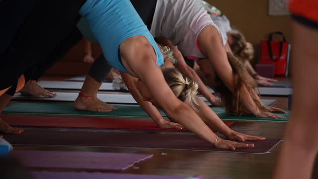 a group of women in colourful yoga clothes stand upright with their arms over their heads and bow into another posture, revealing women sitting behind them on the phone and writing notes, as we see in the foreground the yoga teacher/woman with more women - kelly mason videos stock videos & royalty-free footage