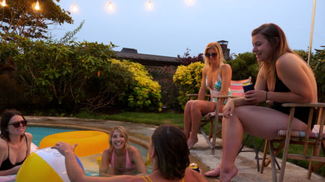 ms group of women in discussion during pool party on summer evening - badebekleidung stock-videos und b-roll-filmmaterial