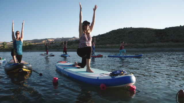 vídeos de stock e filmes b-roll de a group of women in modified warrior 1 yoga pose on paddleboards on a desert lake under a clear, blue sky in western colorado (snooks bottom) - atividade