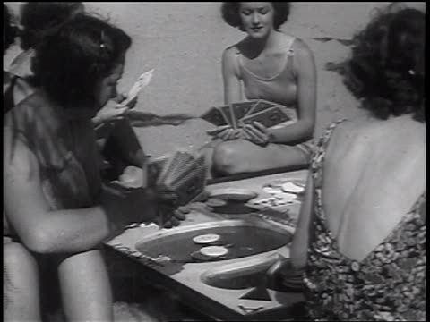B/W 1937 group of women in swimsuits playing card game on beach / newsreel