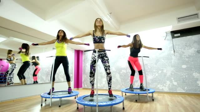 vídeos de stock, filmes e b-roll de grupo de mulheres na academia pulando em um mini trampolim - coordenação