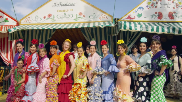 stockvideo's en b-roll-footage met ms cu group of women in traditional sevillana dress posing and waving in front of a casita tented building / seville, andalusia, spain - flamencodansen