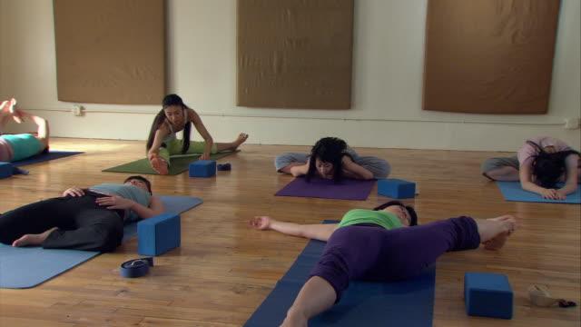 ms pan group of women in yoga class stretching on mats/ new york, ny - linne topp bildbanksvideor och videomaterial från bakom kulisserna