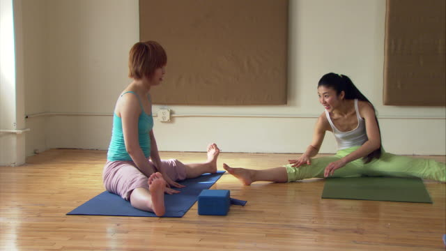 MS PAN Group of women in yoga class stretching on mats/ New York, NY