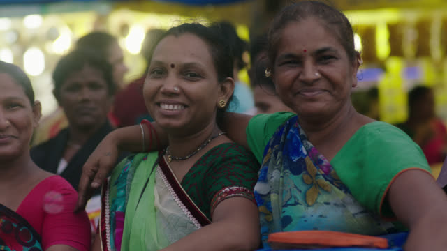 vídeos de stock e filmes b-roll de slo mo. group of women laugh and smile at camera in busy mumbai marketplace. - amizade feminina